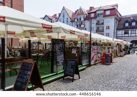 KOLOBRZEG, POLAND - JUNE 23, 2016: Temporary cafes and restaurants covered with a square umbrellas open for the summer season are located on the square in front of town hall - stock photo