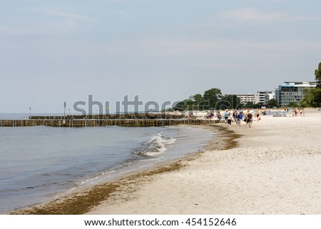KOLOBRZEG, POLAND - JUNE 19, 2016: Unidentified sunbathers enjoy a sunny day on the sandy beach and they are walking along the coast of the Baltic Sea in which there are wooden breakwaters - stock photo