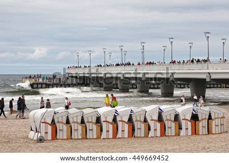 KOLOBRZEG, POLAND - JUNE 26, 2016: Unidentified tourists enjoy their leisure time strolling along the shore of the Baltic Sea, many people enjoy the views from the pier projecting into the sea - stock photo