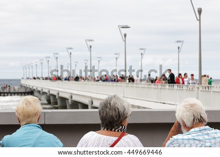 KOLOBRZEG, POLAND - JUNE 26, 2016: Unidentified tourists enjoy their summer time and are watching the people walking along the reinforced concrete pier by the sea - stock photo