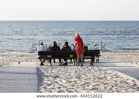 KOLOBRZEG, POLAND - JUNE 20, 2016: Unidentified vacationers have a rest on benches that was set on the sandy beach looking at the vastness of the waters of the Baltic Sea - stock photo