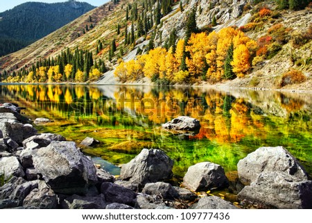 Kolsai mountain lake with yellow trees and reflection in autumn in Kazakhstan, central Asia - stock photo