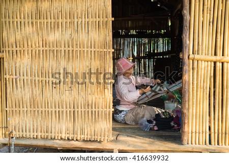 Kon Tum, Vietnam - Mar 28, 2016: Bahnar woman weaves clothing inside of her house in Kon Kotu village, 5km from Kon Tum city