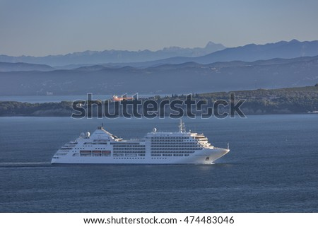KOPER, SLOVENIA - AUGUST 24, 2016: Luxury cruise ship approaching port of Koper with Miramare castle and mountain Triglav in the background