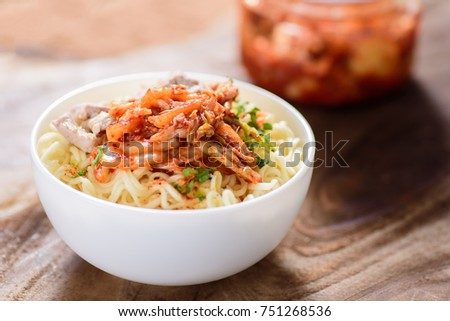 Korean food,instant noodle with kimchi cabbage in a bowl on wooden background