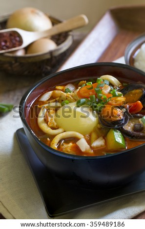 Korean food Suntofu Chigae (Silk Tofu Stew) on wooden table top. - stock photo