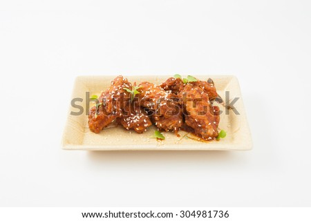 Korean fusion style deep fried chicken wings seasoned with Korean spicy kimchi sauce on square ceramic dish - stock photo