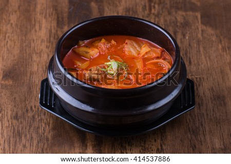 Korean traditional Kimchi soup in a clay pot against wood background