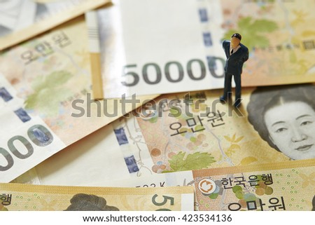 Korean won bill and miniature men - stock photo