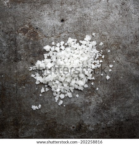 Kosher salt granules on old rustic background, from above - stock photo