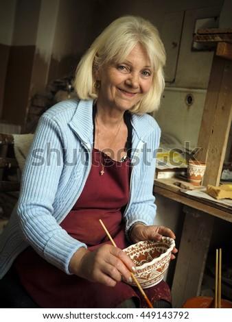 KOSIV, IVANO-FRANKIVSK REGION, UKRAINE - July 15, 2015: artist paints pottery - stock photo
