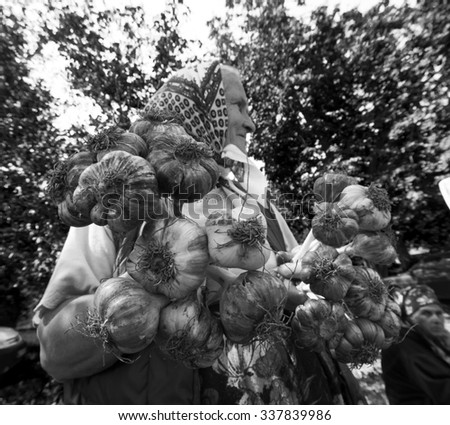 KOSOV, IVANO-FRANKIVSK REGION, UKRAINE - July 16, 2015: elderly woman sells bundles of garlic grown in her own garden, at the farmers market - stock photo