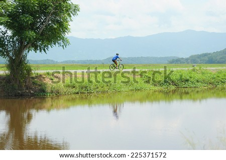 Kota Belud, Sabah Malaysia. October 22, 2014 : A cyclist separated from a large group of Kota Belud Jamboree 2014, cycling alone along the gravel road near Sangkir paddy field in Kota Belud Sabah. - stock photo