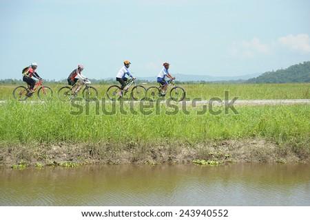 Kota Belud, Sabah Malaysia. October 22, 2014 : A group of cyclist cycling along gravel road near Kampung Sangkir paddy field in Kota Belud Sabah. - stock photo
