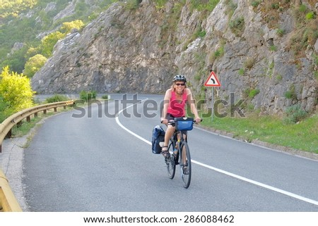 KOTOR, MONTENEGRO - YULY 17: A smiling woman cycling with the panniers on a mountain road of Kotor Bay. Shot in 2014  - stock photo