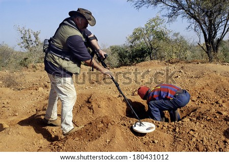 KOUPELA, BURKINA FASO - JANUARY 9: wild golden Koupela mine, the gold diggers come from everywhere to dig, a French or researcher works with a powerful metal detector, january 9, 2008. - stock photo