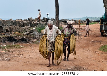 KOVALAM, INDIA - DEC 28, 2014: Unidentified Fishermen with a rope for fishing net  on Samudra beach in Kovalam. Kerala. India