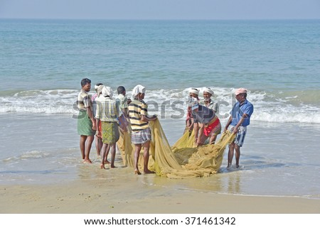 KOVALAM, KERALA, TRIVANDRUM, INDIA, FEBRUARY 03, 2016: Fishermen pulling up the net to find a disappointing harvest. A scene in the morning on the beach at Kovalam. Poor harvest. - stock photo