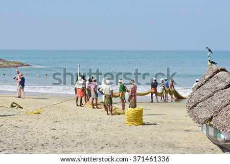 KOVALAM, TRIVANDRUM, KERALA, INDIA, FEBRUARY 03, 2016: Fishermen pulling up the net to find a disappointing harvest. A scene in the morning on the beach at Kovalam. Tourists and locals. - stock photo