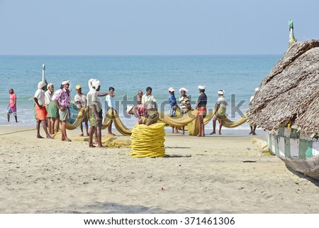 KOVALAM, TRIVANDRUM, KERALA, NDIA, FEBRUARY 03, 2016: Fishermen pulling up the net to find a disappointing harvest. A scene in the morning on the beach at Kovalam. Protecting head from hot sun. - stock photo