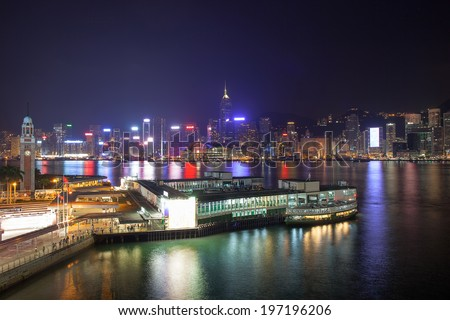 Kowloon Ferry Pier at Tsim Sha Tsui with Hong Kong Island Central City Skyline at Night - stock photo