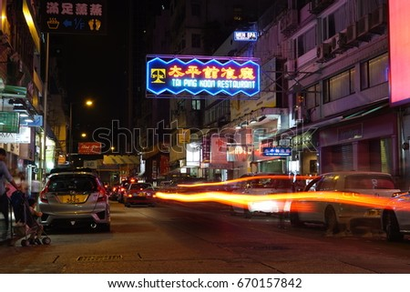 KOWLOON, HONG KONG - MAY 14, 2017: Hong Kong Taxi cabs drive past a colorful neon sign.