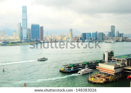 Kowloon island at sunset.  Ferry pier from Hong Kong to Macao on the right.  - stock photo