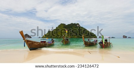 Krabi, Thailand - July 26, 2014: Long tail wooden boats (traditional way of transport) and boat operator with island background and blue sky in Tup island, one of Krabi's nearest island with people.