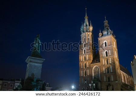 Krakow in Poland at night. St Mary's Basilica (Mariacki Church) and Adam Mickiewicz monument on Main Square in the Old Town. - stock photo