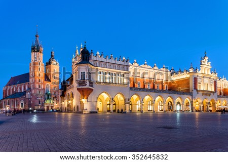 Krakow - Poland - April 22.  Evening view of Mariacki Church and Hall with markets inside the hall. People walks on old square. Panoramic view. Krakow - Poland - April 22, 2015