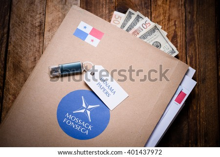 KRAKOW, POLAND - APRIL 5, 2016 : Folder with Mossack Fonseca logo and US and EU currency with flash drive. Panama Papers are millions leaked documents with information about offshore companies.
