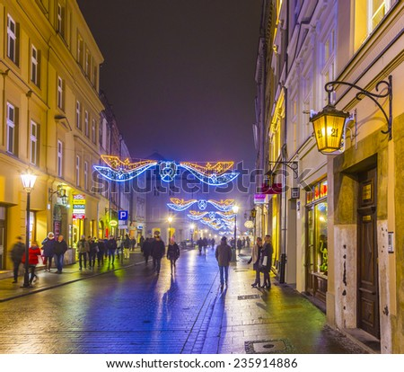 KRAKOW, POLAND - DECEMBER 5, 2014: City center by night: people at Rynek Glowny square druring christmas fair, Krakow, Poland.