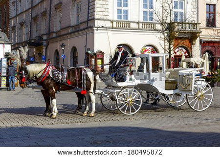 KRAKOW, POLAND - FEBRUARY 26, 2014: Horse-drawn carriage at the Market Square, from January 01, 2013 standardized the color, total length of no more than 7.0 m, can be harnessed to a max of two horses