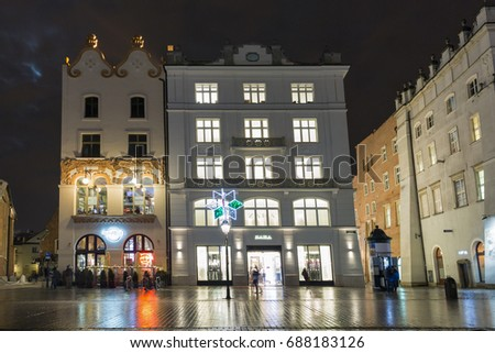 KRAKOW, POLAND - JANUARY 12, 2017: People walk along Hard Rock Cafe and Zara store on Main Market square in old town at night. Krakow is the second largest and one of the oldest cities in Poland.