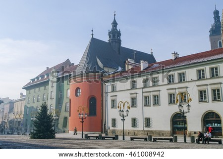 Krakow, Poland - January 6, 2011: The rounded coral-colour choir of St. Barbara's church flanked by 17-18th century mansions in the Maly Rynek (Little market square)