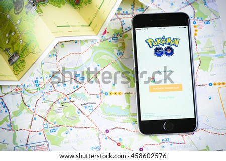 Krakow, Poland - July 25, 2016 : Apple iPhone 6 mobile phone with popular game Pokemon Go running on screen over Krakow city map and folded map of surroundings. - stock photo