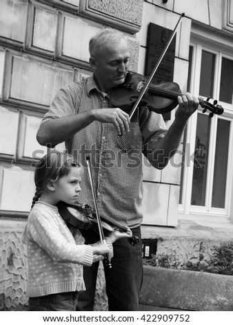KRAKOW, POLAND - July 27, 2014: the man and girl playing violin on the street in Krakow