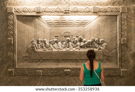 "Krakow, Poland - May 16, 2013. Tourist visiting Wieliczka Salt Mine in Krakow, Poland, Europe. Woman looking at Leonardo's ""The Last Supper"" carved in a wall of rock salt in Unesco heritage site."