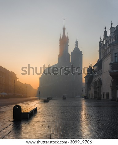 Krakow, Poland, St Mary's church and Sukiennice (Cloth hall) on the Main Market Square in morning fog illuminated by rising sun - stock photo