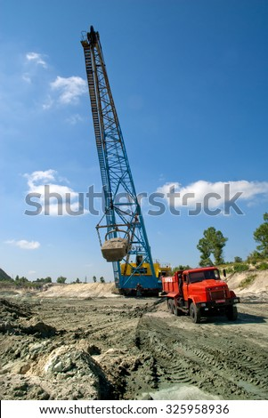 Kremenchug, Ukraine - 27 June 2008. Excavator loading iron ore into the heavy dump truck on the iron ore opencast mining - stock photo