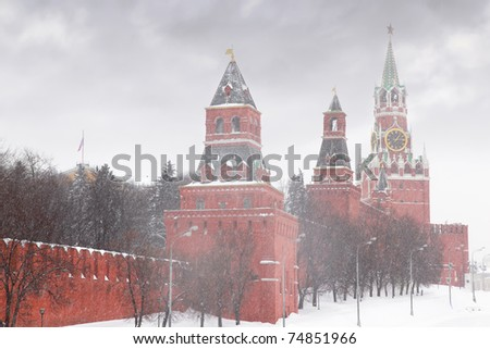 Kremlin chiming clock of the Spasskaya Tower in Moscow, Russia at wintertime during snowfall - stock photo