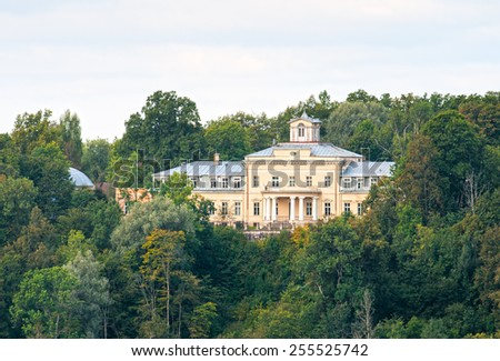 Krimulda Palace on the hill in the dense forest - stock photo