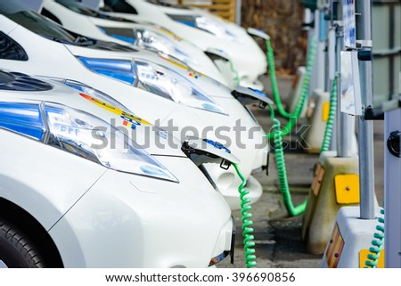 Kristianstad, Sweden - March 20, 2016: The charging of some white Nissan electrical cars. Green coiled cables are attached to the front of the cars. These are C4 Energi carpool rentals. - stock photo