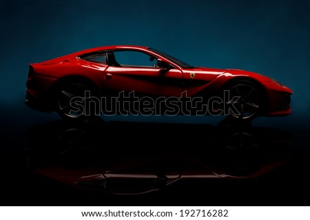 KRIVOY ROG, UKRAINE - JAN 04 - Toy ferrari F12 berlinetta on black background, Saturday 4 January 2014 - stock photo
