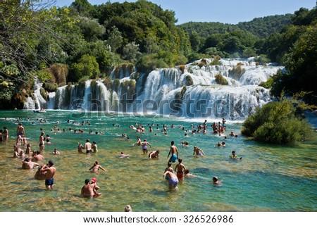 KRKA NATIONAL PARK, CROATIA - AUG 10, 2012: Tourists swim in the Krka River in the Krka National Park in Croatia. It is one of the National Parks in Croatia - stock photo