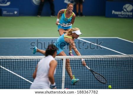 KUALA LUMPUR - APRIL 19, 2014: Olga Savchuk and Lyudmyla Kichenok (white cap) take to the center court in the women's semifinals of the BMW Malaysian Open tennis is Kuala Lumpur, Malaysia. - stock photo
