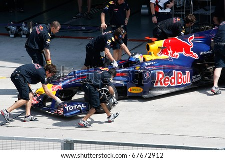 KUALA LUMPUR - APRIL 2: Red Bull team mechanics push Sebastian Vettel's car back into the garage on practice day at the 2010 Petronas Malaysia F1 Grand-Prix on April 2, 2010 in Sepang, Malaysia.