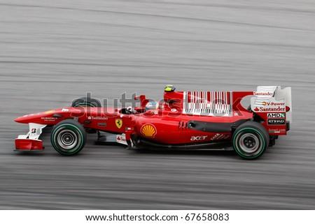 KUALA LUMPUR - APRIL 4: Scuderia Ferrari driver Fernando Alonso takes the hairpin turn on race day at the 2010 Petronas Malaysia Grand-Prix on April 4, 2010 in Sepang International Circuit, Malaysia. - stock photo