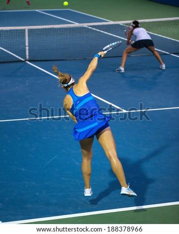 KUALA LUMPUR - APRIL 20, 2014: Timea Babos of Hungary (blue) serves during the doubles final of the BMW Malaysian Open Tennis in Kuala Lumpur, Malaysia. She partners Chan Hao-Ching to emerge winners. - stock photo