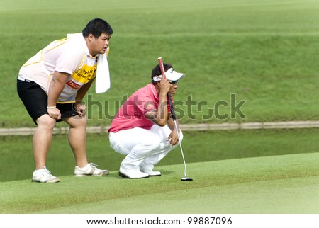 KUALA LUMPUR - APRIL 12: Tongchai Jaidee(THA/right) discussing with his caddy during tournament Maybank Malaysian Open 2012 day 1st at Kuala Lumpur Golf & Country Club on April 12, 2012 in Kuala Lumpur, Malaysia.